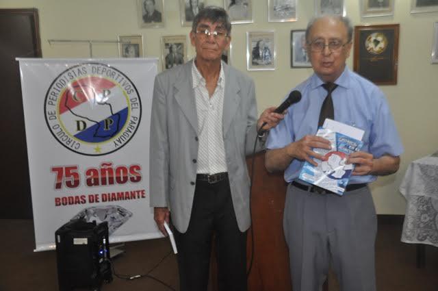 """Juan Crichigno (der.) expone con libro en mano de su autoría """"Crónica en el Círculo"""". Foto."""